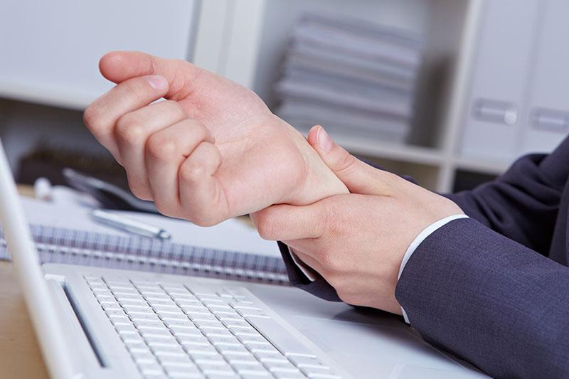 Person im Büro am Laptop mit Handgelenksschmerzen