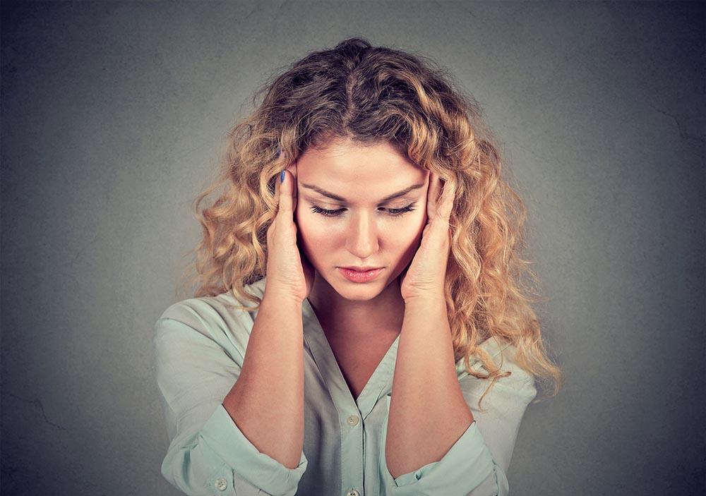 Junge Frau mit Migräne Kopfschmerzen fasst sich mit beiden Händen an die Schläfen
