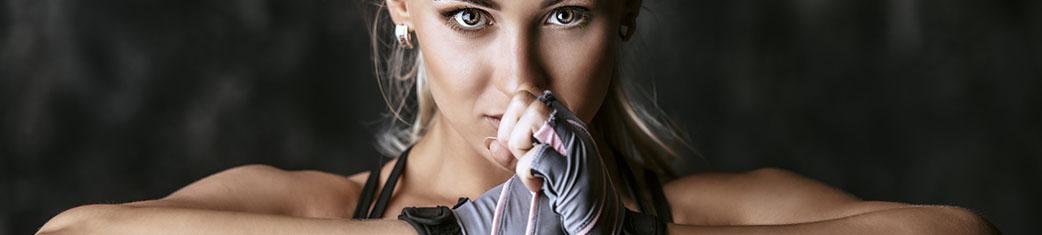 sportliche junge Frau von vorne mit direktem Blickkontakt, die ihre Hände vor dem Gesicht zusammendrückt