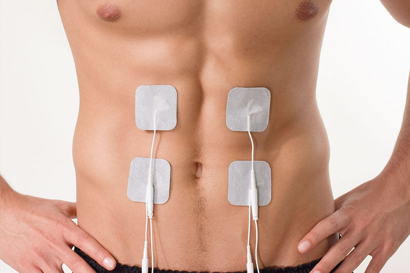 Männlicher durchtrainierter Bauch mit Elektroden auf den Bauchmuskeln Sixpack