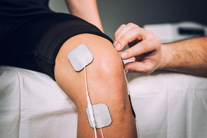 Knie einer Person mit TENS Elektroden die von einem Therapeuten geklebt werden