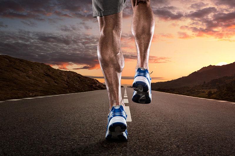 joggende Person die auf einer Straße in den Sonnenuntergang läuft