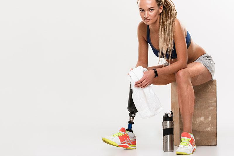 sportliche Frau mit einer Beinprothese sitzt auf einer Box