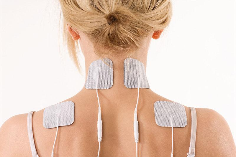 Schulter- und Nackenbereich einer Frau mit TENS EMS Elektroden