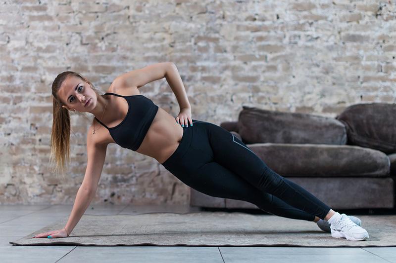 Sportliche junge Frau macht seitliches Hüftheben als Bauchmuskeltraining in einer coolen Location
