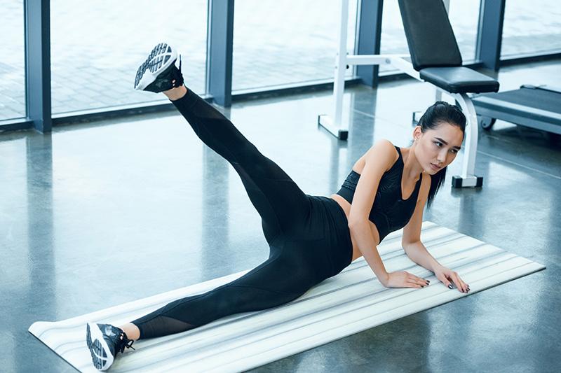junge sportliche Frau macht Bauchmuskeltraining mit der Übung Seitliches Beinabsenken in einem Fitnessstudio