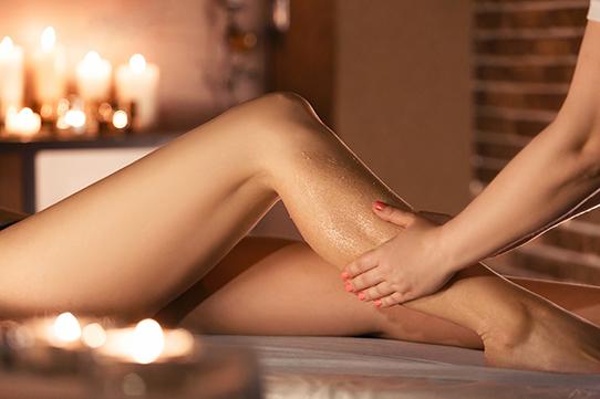 Bei erholsamen und ruhigem Kerzenlicht werden Beine massiert