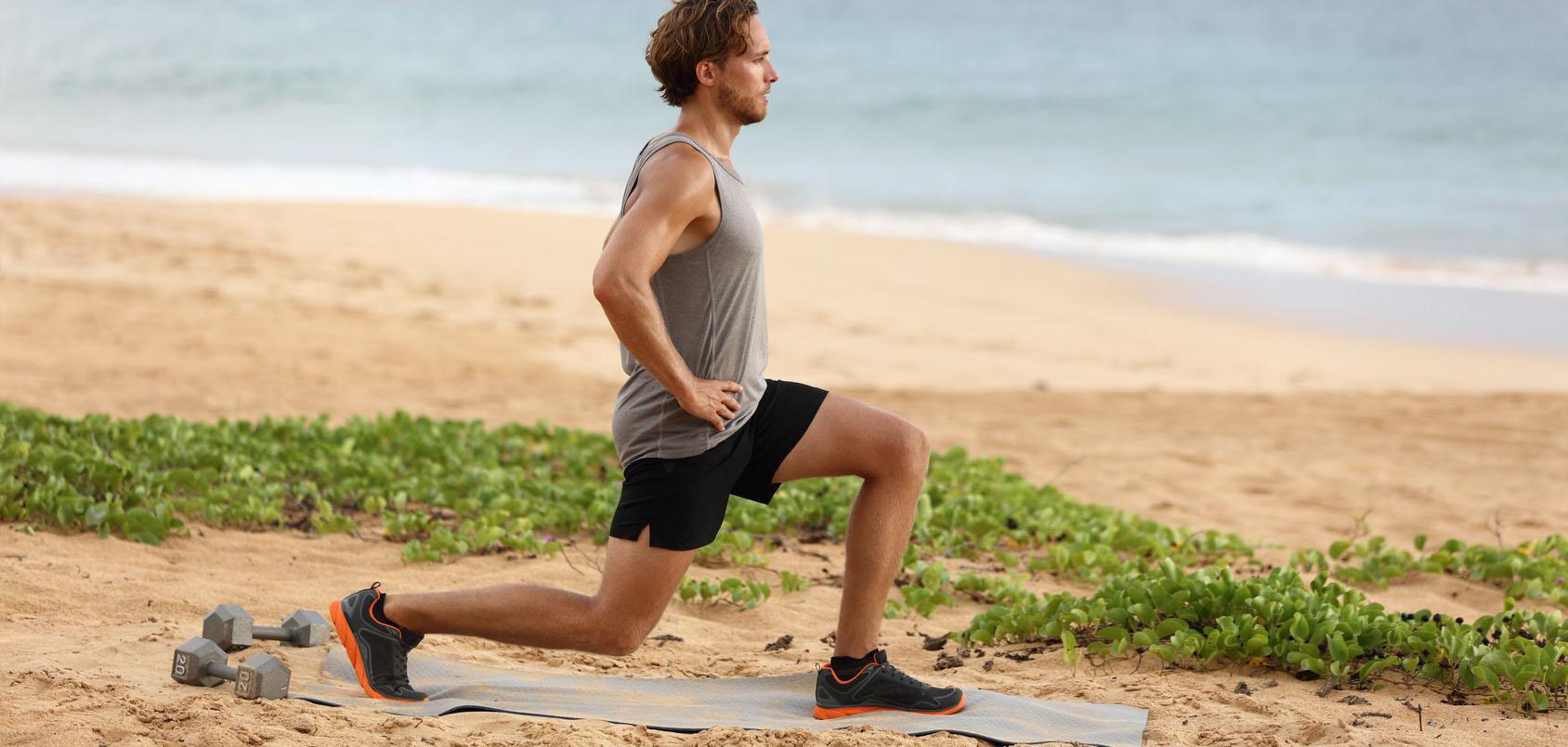 junger sportlicher Mann am Strand macht Oberschenkeltraining mit Ausfallschritt