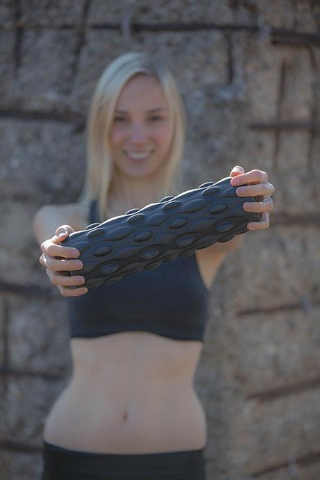 junge sportliche Frau mit Faszienrolle SaneoROLL+ im Vordergrund