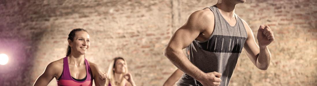 Mehrere Personen die in einem Fitnessstudio Stepperübungen machen