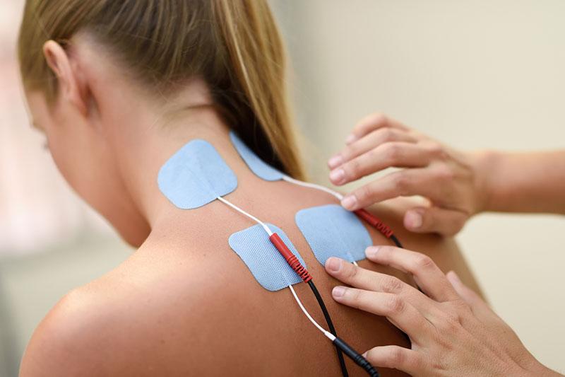 Frau mit TENS Klebeelektroden im Nackenbereich zur Schmerzlinderung