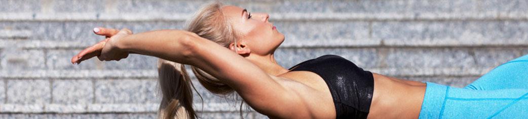 sportliche junge Frau macht vor einer Treppe Faszientraining mit der Faszienrolle SaneoROLL+